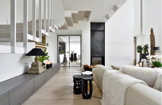 Obývací pokoj je vybaven atypicky upravenou krbovou vložkou. Hned vedle na stěně za bílým výsuvným panelem se skrývá televizor a další audio příslušenství. Dřevěná podlaha je z běleného dubu a katrovaná