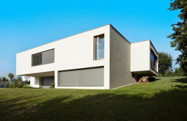 Kompozici domu člení výrazné přesahy hmot. Obývací pokoj v patře přesahuje nad vstupem do domu a vjezdem do garáže a tvoří velké chráněné závětří