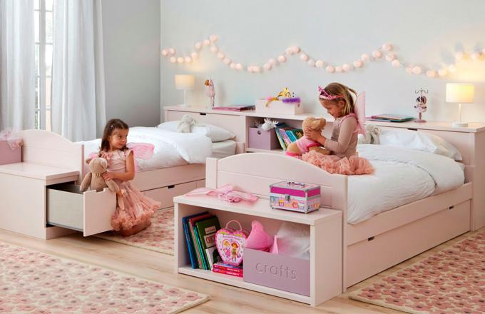 Dětský pokoj se dvěma postelemi, jedna s výsuvnou postelí, druhá s úložnými zásuvkami, v záhlaví úložné prostory na lůžkoviny a knihovnička