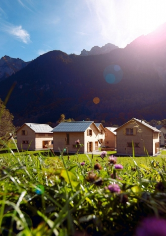 V alpském údolí na rozkvetlé louce se dvanáct roztomilých dřevených domečků krásně vyjímá