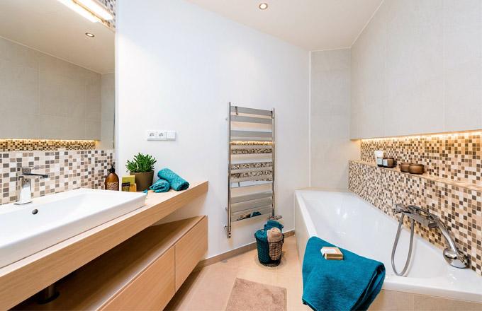 Ladění koupelny v neutrálních přírodních tónech podtrhují doplňky ve výrazných barvách, které mohou majitelé podle libosti obměňovat