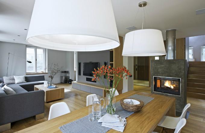 Odstíny bílé a šedé barvy působí čistě a jednoduše, díky kombinaci s dubovým dřevem však prostor nevypadá stroze