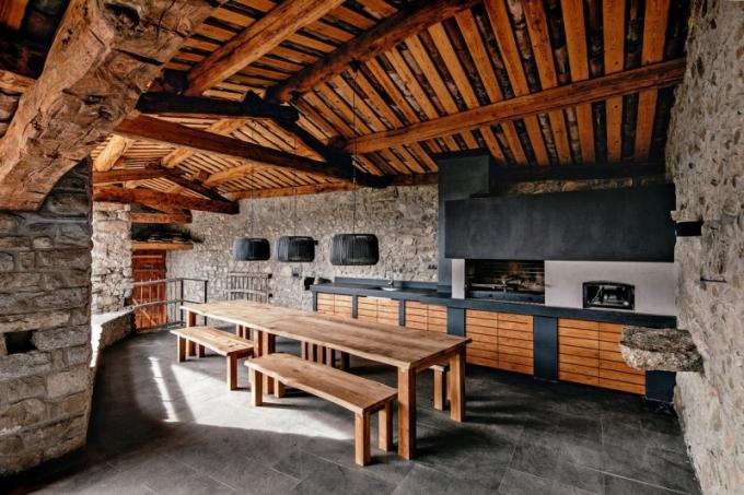 Venkovní kuchyň je vybavena jednoduchými dřevěnými lavicemi
