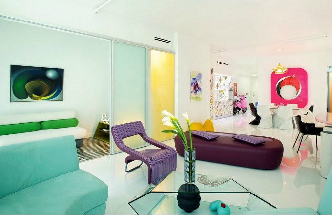 Obývací pokoj má otevřenou dispozici a je propojený s kuchyní. Zařízený je především nábytkem podle návrhu Karima Rashida doplněným růžovým hliníkovým artefaktem od německého umělce Gerolda Millera na stěně za jídelním stolem