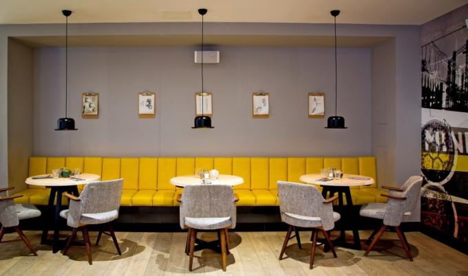 Jedna z podob restaurace Parts and Labour. Posnídat můžete u malých kulatých stolků na žlutých lavicích nebo šedých křesílkách, ale stejně dobře si tu můžete dát i oběd, pokud vás nezláká jiný kout, třeba v blízkosti plápolajícího ohně v krbu