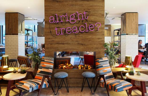 Hostům je k dispozici i hotelová knihovna. Výrazný neon a barevná křesílka zvou ke společnému čtení