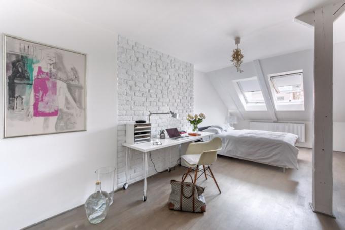 Pracovna slouží i k příležitostnému přespání návštěv. Také zde byla částečně obnažená cihlová stěna natřená bílou barvou. Dlouhý stůl zhotovený na míru s využitím kolečkových noh z Ikea je doplněn ikonickou židlí DAW od Charlese a Ray Eamesových