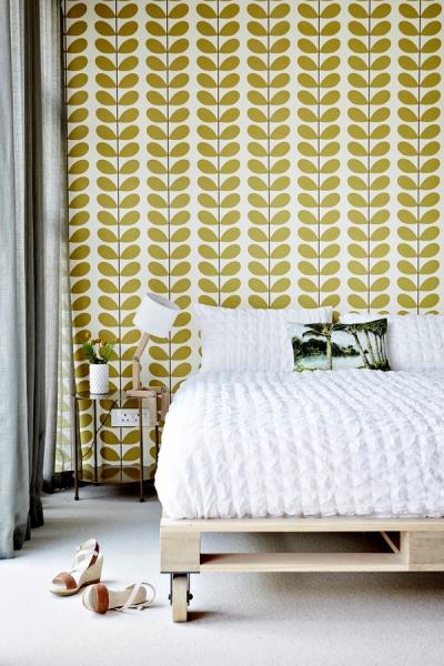 Přírodní světlé odstíny dominují i ložnici. Pohled přitáhne jednoduchá dřevěná postel na kolečkách a stylově ladící stolní lampa