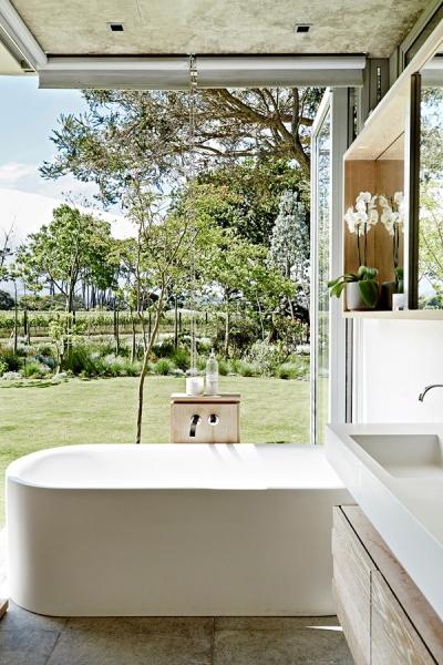 Hlavní minimalisticky zařízená koupelna je otevřená do zahrady a koupající si musí nesmírně užívat ničím nerušený výhled do zeleně. Jednoduché čisté linie jsou jediným možným řešením, protože hlavní dekorací je příroda sama