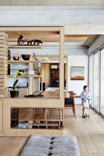 Otevřený prostor společné části domu je ideální pro Ollieho a jeho malou koloběžku. Jednotlivé zóny jsou opticky odděleny vtipně řešeným policovým regálem