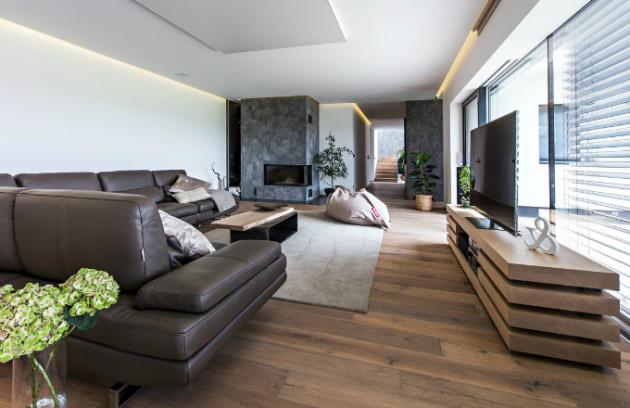 Prostor obývacího pokoje příjemně ozařuje nepřímé osvětlení po obvodu místnosti