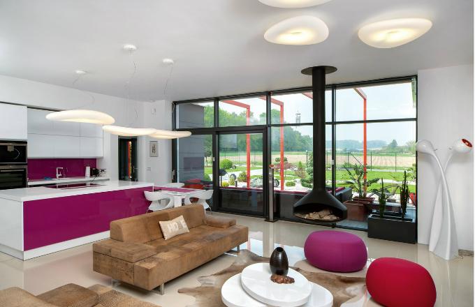 Barevný kontrast, červenofialové sklo Lacobel na kuchyňské lince, čalounění v obdobném odstínu a zavěšený krb z černého plechu, oživuje vzdušný interiér, v němž hrají hlavní roli bílá barva a světlá velkoformátová leštěná dlažba
