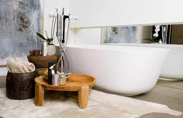 Okolo vany umístěné ve vyšší úrovni jsou ručně opracované doplňky z teakového dřeva, jako předložka slouží krémově zbarvená kožešina