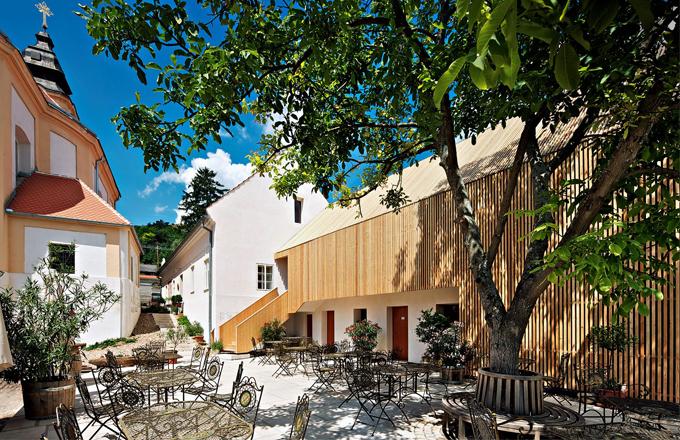Původní i nově postavené budovy obepínají dvůr, jemuž dominuje vzrostlý kaštan. Restaurovaná architektura je doplněna moderní dřevěnou stavbou