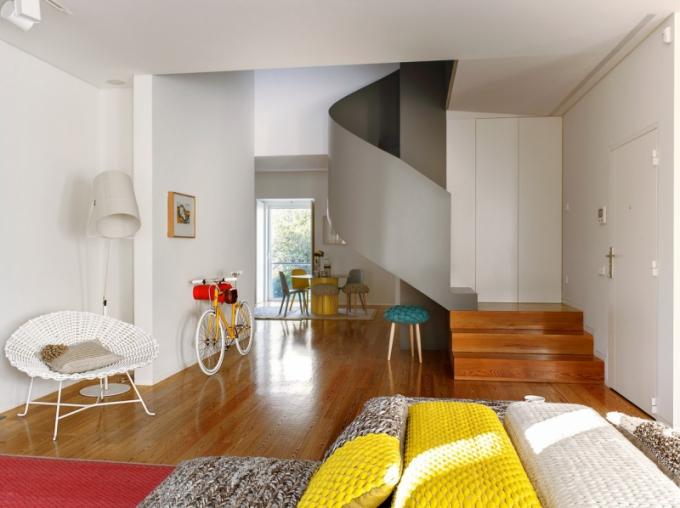 Točité schodiště z lakovaného kovu vede k ložnicím. Malou chodbu spojující obývací pokoj s jídelnou a kuchyní vybavila designérka bílou židlí značky Gervasoni a lampou od Foscarini. Tyrkysová stolička stojící bezprostředně vedle schodiště je z produkce Gandía Blasco