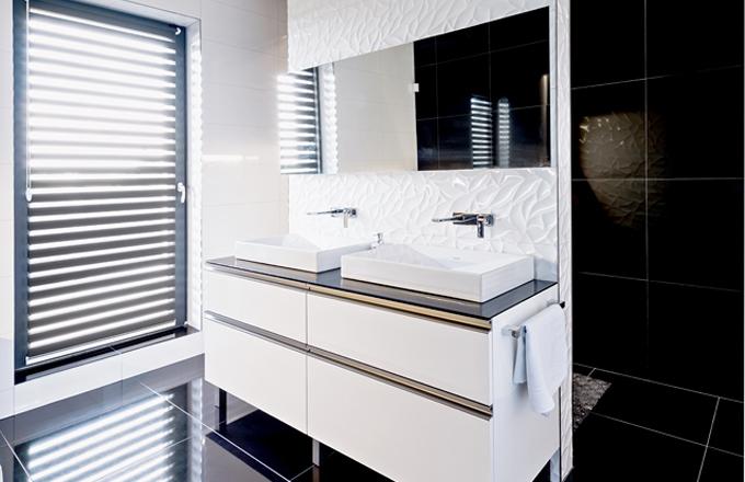 V zadní části za dělicí příčkou ukrytá toaleta, v přední je sprchový kout. Na příčce je použitý reliéfní obklad Oxo Deco Blanco z kolekce Marmi (Porcelanosa), cena 2 396 Kč/m2