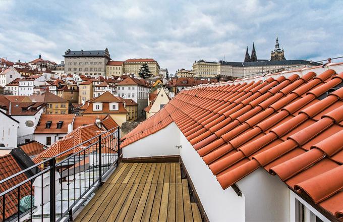 """Terasa je zapuštěna do střechy, takže nijak nenarušuje celkový vzhled domu. Vstupuje se na ni oknem, ale výhled na Petřín, Pražský hrad a jeho okolí za to drobné nepohodlí rozhodně stojí. Jakub Cigler nám terasu představil jako svůj """"letní obývák"""""""