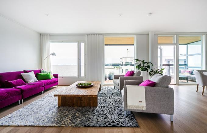 Byt je dispozičně řešený jako otevřený prostor s velkolepým výhledem na moře. Obývací pokoj je vybavený pohovkou Donna (HTCollection) ve fuchsiové barvě doplněnou šedými křesly stejné značky. Teakový stůl stojí na šedém koberci od Designer´s Guild