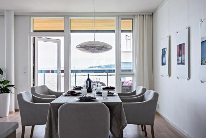 Větší jídelní stůl je doplněný židlemi Roma od Furninovy v příjemném šedém odstínu. Stěny zdobí na jemných drátech zavěšené fotky od Charlotty Boucht