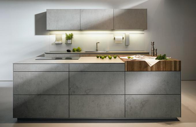 Díky novému výškovému rozměru skříňky, snížení soklu o 5 cm a otevírání TIP-ON se dosáhlo moderního a minimalistického vzhledu kuchyně NX950 v designu šedého betonu.
