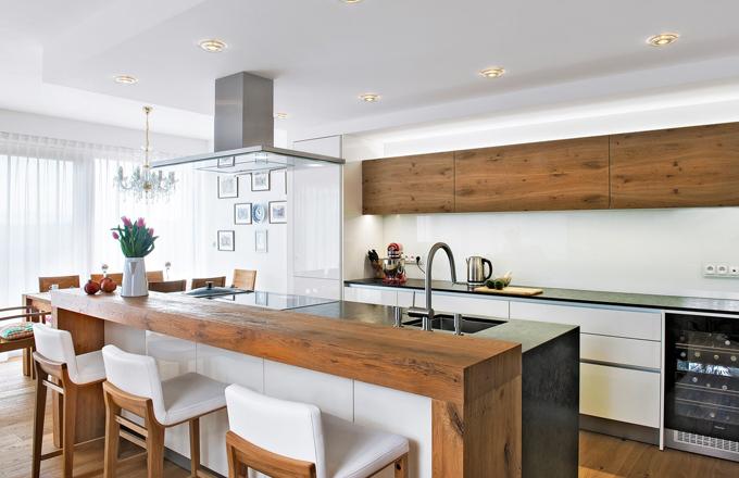 V otevřeném společném prostoru propojeném s kuchyní a obývákem se vaří, stoluje i odpočívá. Prosklená stěna za jídelnou nabízí vstup do zahrady