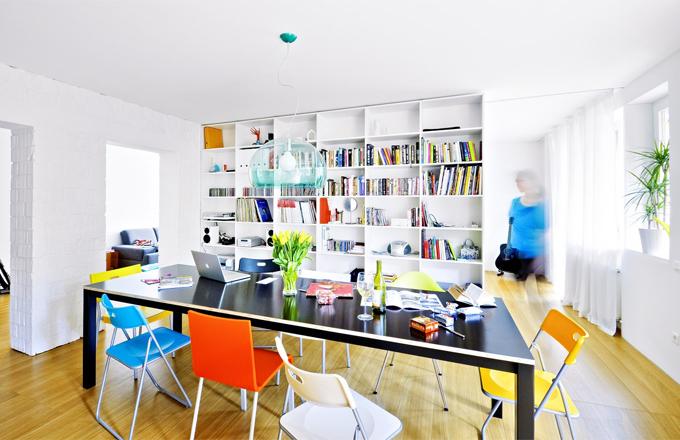Otevřenost prostoru je hlavním atributem bytu. Základní tříbarevnost -přírodní buk, bílá, černé plochy - je rozbita různě barevnými židlemi