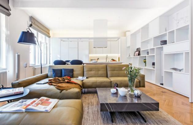 Členitá knihovna z bíle lakované MDF desky pokrývá celou jednu stěnu místnosti. Koženou sedací soupravu Rolf Benz doplňuje stojací lampa Tolomeo od Artemide