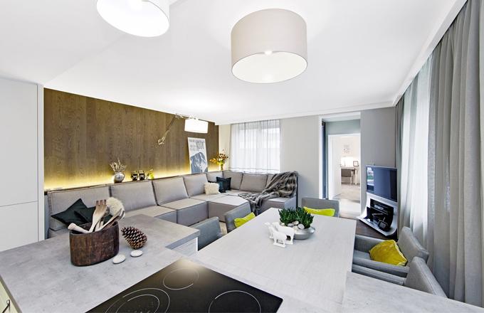 Výrazným prvkem hlavní obytné části je dřevěný obklad stěny, který si v městském bytě těžko dovedeme představit, ale v horském apartmánu působí zcela přirozeně a patřičně. Vyhotoven je ve stejném dekoru jako podlaha a jeho nepřímé osvětlení dotváří příjemnou a teplou atmosféru celého prostoru. Rozměrná pohovka byla vyrobena na míru podle návrhu Wawa design