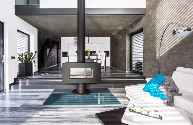 Velký otevřený prostor v přízemí nabízí celé rodině místo k odpočinku v obývacím pokoji se sedačkou a také místo ke společnému stolování a majitelce i k vaření