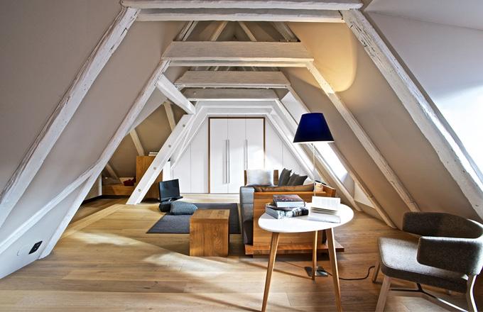 Podlahu interiéru kryjí dřevěná prkna z běleného dubu. Ve štítové zdi obývacího pokoje, který volně přechází v ložnici, je třídílná skříň s dalšími úložnými prostory