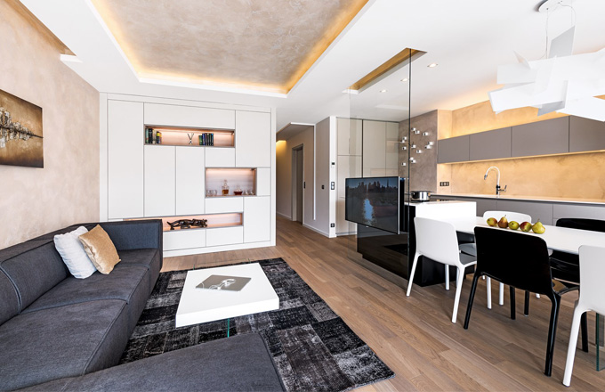 Součástí obývacího pokoje je nábytková stěna lamino desek s osvětlenými nikami a stolek integrovaným lihovým krbem, obojí zhotovené podle návrhu architekta, a antracitová sedací souprava Carmo. Televizor zdánlivě levituje prostoru před kuchyňským ostrůvkem. Je zavěšený na čiré stěně z bezpečnostního skla