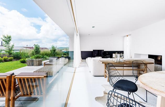 Otevřený interiér propojuje dubová kartáčovaná podlaha z bíle olejovaných prken. Částečně ji místy překrývají hovězí kožešiny a ručně tkané koberce