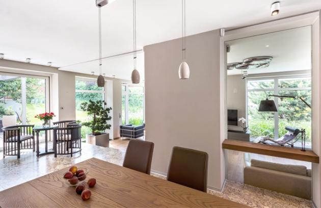 V obývacím pokoji se skvěle vyjímá ikonická chaise longue LC4 Le Corbusiera, Jeannereta a Perriandové. Místnost osvětlují přisazená stropní LED svítidla Duel (Modular), designové stropní svítidlo Mercury navržené designérem Rossem Lovegrovem a ikonická lampa Tolomeo (Artemide). Interiér osvěžují velké rostliny posazené do nerezových květináčů Kasper