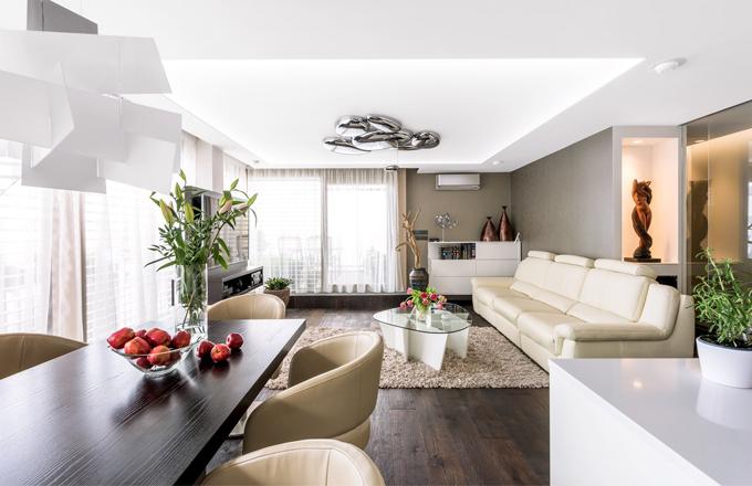 Prostor bytu sjednocuje olejovaná dubová podlaha Kährs rustikálního vzhledu, drásaná a mořená do tmavého odstínu. Prostoru vévodí stropní svítidlo Mercury (Artemide) přisazené na části stropu z barrisolu. Na stěnách jsou částečně použity tapety. V nice nad vinotékou (Miele) našla své výsadní postavení umělecká dřevěná soška