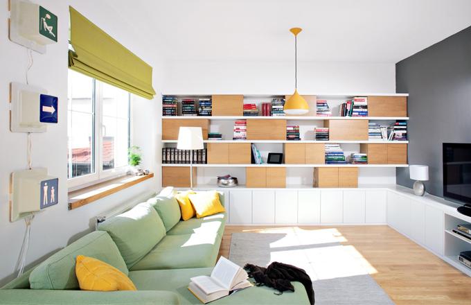 Nábytek vyrobený na míru kombinuje bílé lamino a dubovou dýhu. Jednotící prvek je zřejmý jak u knihovny v obývacím prostoru, tak u dělicí stěny mezi kuchyní a jídelnou, najdeme ho i v ložnici, koupelně a úložných skříňkách