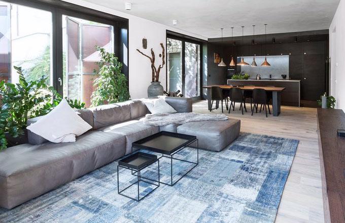 Dostatek přirozeného denního světla a propojení interiéru s exteriérem celý prostor opticky zvětšuje. Efektně působí také kuchyň na míru z černě mořeného dubu pokrývající celou jednu stěnu místnosti, která tvoří harmonický kontrast s převažující bílou výmalbou a pokoj vizuálně prohlubuje
