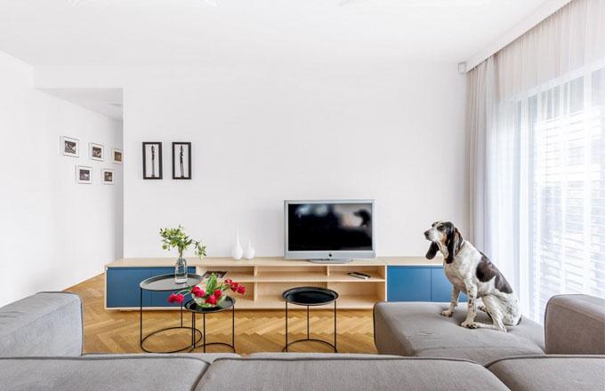 Obývací pokoj je vybavený nábytkem zhotoveným na míru podle návrhu architektky. Barevný akcent modré se sem propisuje z kuchyně a umocňuje kompaktnost celku