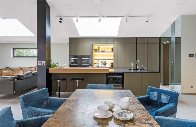Velký jídelní stůl (2,4 x 1,2 m) na kovové podnoži zhotovený z travertinu Tabaco je vyrobený podle návrhu Jaroslava Harmáčka. Je vyhřívaný, vybavený datovými kabely a ovládáním osvětlení. Obklopují ho židle (Ikea) s područkami potažené snímatelnými povlaky ušitými ze starých jeansů, které sem navrhla paní domu