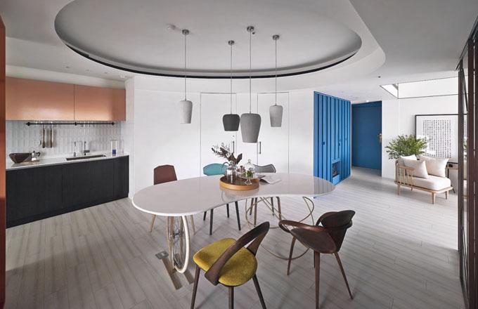 Pomyslným středobodem bytu je asymetrický jídelní stůl, jehož podnoží je volně inspirováno konstrukcí šicího stroje