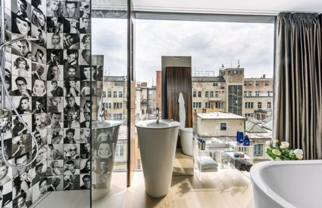 Prosklená obvodová plocha poskytuje v koupelně výhled na brněnské centrum. Jediným kusem nábytku je transparentní stolek
