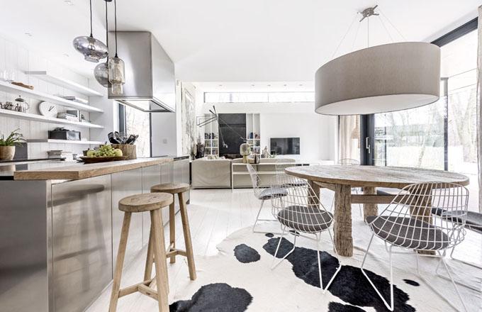 Kulatý jídelní stůl s průměrem 160 cm je zhotovený podle autorského návrhu architekta Martina Franka ze starého jilmového dřeva. Je doplněný kovovými židlemi Pastoe a zasednout k němu může až osm osob