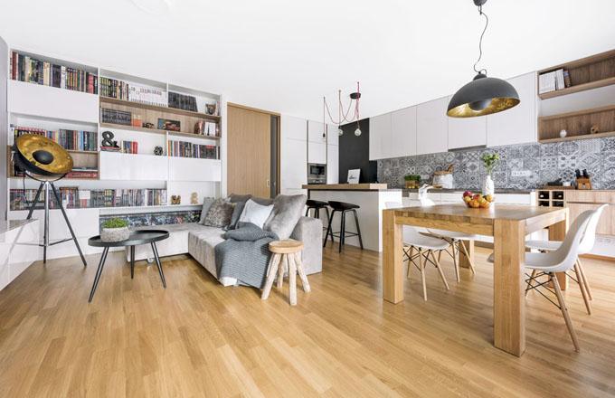 Největší pokoji v bytě slouží jako kuchyň, jídelna, obývací pokoj i pracovní kout. S medovým tónem dubové podlahy se dokonale doplňuje masivní dřevěný stůl, bílý nábytek a šedá barva na potahu sedačky a obkládačkách