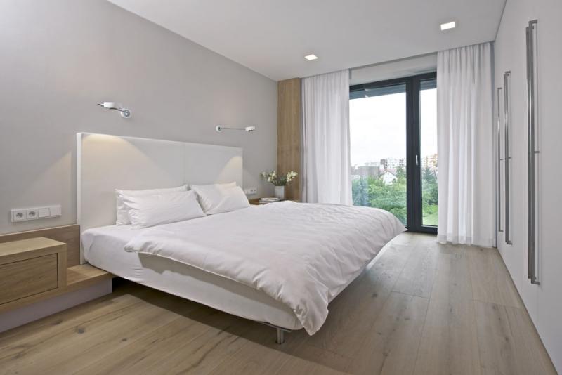 Ložnice je orientována s výhledem do zahrady. Nábytek včetně lůžka je zhotovený na míru z lakované MDF desky v kombinaci s bělený dubem. Postel doprovázejí lampičky Occhio