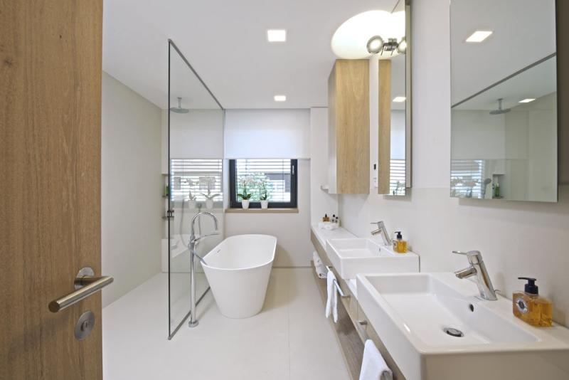 Koupelna nabízí dostatek místa při sprchování i možnost koupele ve vaně (Riho) z kompozitního materiálu. Je obložená dlažbou Cerdisa (1 x 3 m) a nábytek je zhotovený na míru. Umyvadla Duravit jsou posazená na kompozitní desce z materiálu Staron a doplněna bateriemi Hansgrohe