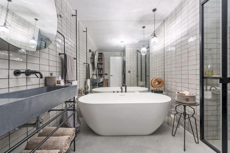 Z niky, která byla původně určená pro pračku se sušičkou, je dnes sprchový kout s atypickou černou sprchovou zástěnou, která se zde stylově potkává s dalšími ocelovými prvky z ohýbané tyčoviny. Zrcadlo je možné podle potřeby naklopit