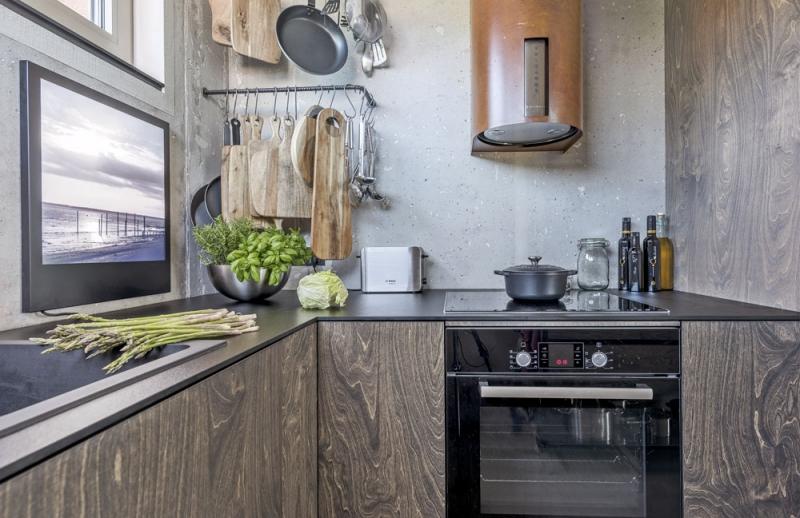 K praktickému uložení některého náčiní slouží nástěnné držáky zhotovené z roxorů. Nábytek v kuchyni je vyrobený na míru z voděvzdorné překližky ošetřené černým olejem. Digestoř je opláštěná speciálně upraveným zkorodovaným plechem