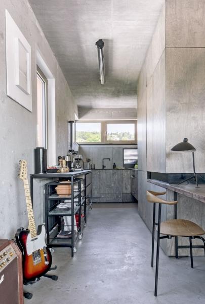 Industriální charakter prostředí podporuje litá podlaha z cementové stěrky a obnažený beton na stěnách. Pro zachování vzdušnosti nejsou v kuchyni použity horní skříňky. Dostatek úložných prostorů i přidanou pracovní plochu nabízí úzký nábytkový modul s policemi z drátoskla a kontejnery na kolečkách podle autorského návrhu architektky Dagmar Štěpánové