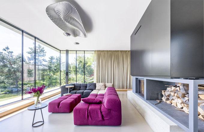 Litá podlaha ze stěrky Mapei v obývacím pokoji je zanořená hlouběji do země a kolem rámovaná navazující krytinou z třívrstvých dubových lamel, ukrývající konvektory