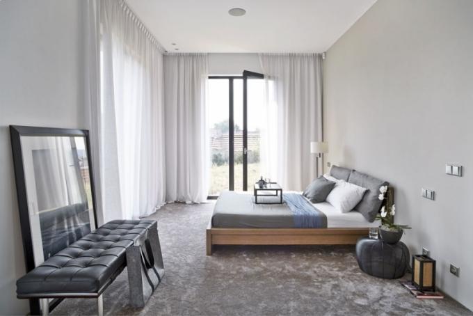 Ložnice orientovaná jihozápadním směrem má prosklené stěny a nabízí uklidňující pohled do zeleně. Komfort a útulnost podporuje celoplošný hedvábný koberec