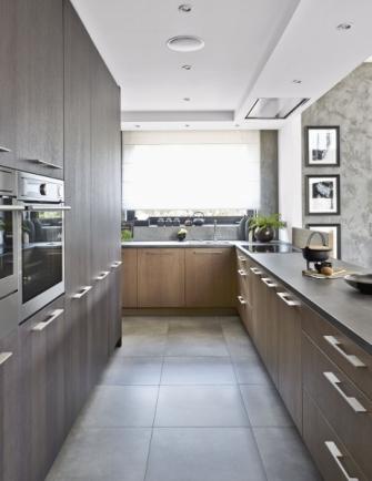 Povrch kuchyňské sestavy nábytku je vyroben z mořeného dubu a podlaha z velkoformátové dlažby imitující beton. I odtud je krásný výhled do zahrady